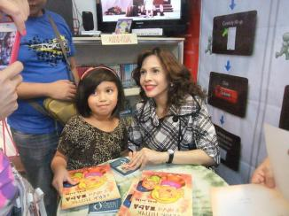 "ms. rita avila during the signing of her book- ""Si Ana Tutpik At Si Erik Taba"" with a female kid."