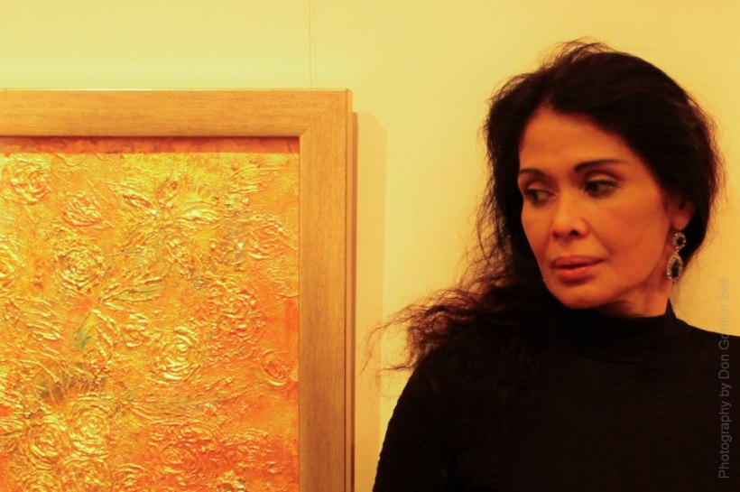 """ms. evangeline pascual poses beside her """"gold flower leaf"""" painting"""