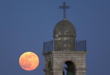 The moon is seen rising behind the Mar Elias Greek Orthodox Monastery in Jerusalem on June 23, 2013.