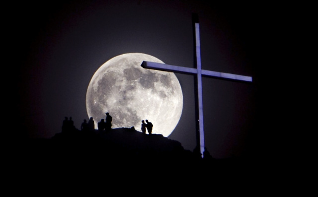 """A """"supermoon"""" rises over Table Rock and the lighted cross near Boise, Idaho, Saturday night, June 22, 2013.   The larger than normal moon called the """"Supermoon"""" happens only once this year as the moon on its elliptical orbit is at its closest point to earth and appears 13.5 percent larger than usual. (AP Photo/The Idaho Statesman, Kyle Green)  LOCAL TV OUT (KTVB 7)"""