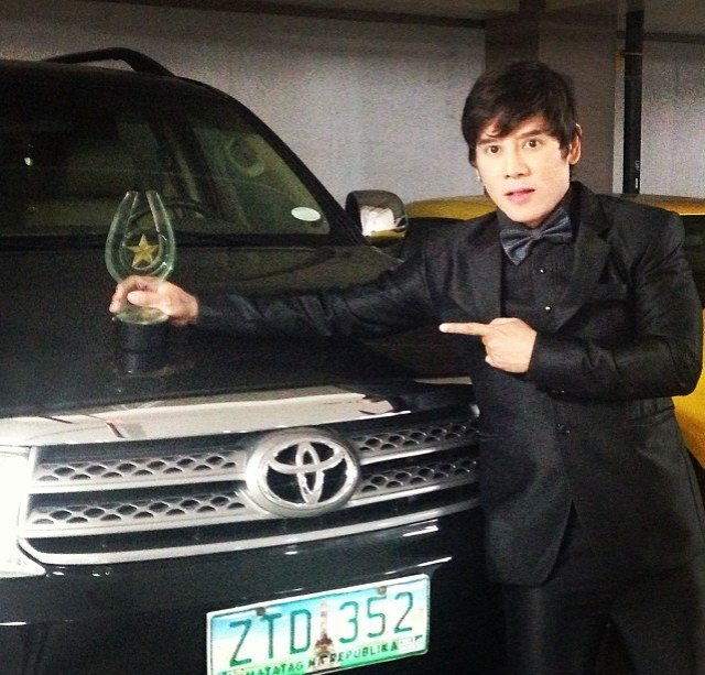 "vince tanada, with his signature black car, in a black suit and holding his most precious award to date- his trophy as the Best New Male Actor for the movie ""Otso"", given by Philippine Movie Press Club"