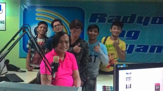 mommy renee garcia (in pink shirt) poses with thomas, jv, vince, patrick and johnrey. at the backdrop is the radyo ng bayan wall logo