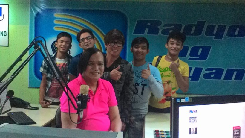 mommy renee garcia (in pink shirt) poses with thomas, jv, vince, patrick and johnrey. at the backdrop is the radyo ng bayan wall logo