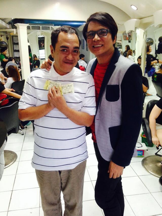 "this blogger holding his winning tickets from ccp for ""beauty & the beast"", as he poses with ness astilla at the latter's beauty salon"