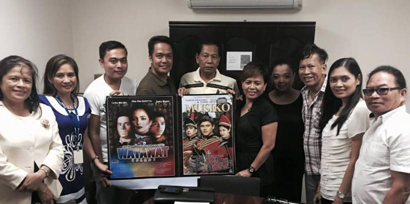 "dave with filipino-australian community members holding the posters of his other films ""musiko"" and ""watawat"""